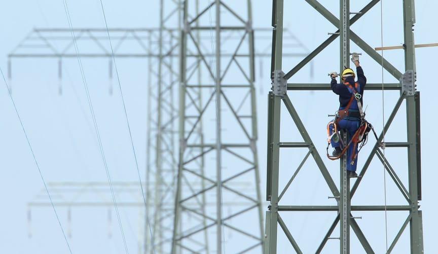 man climbing transmission tower